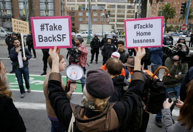 A woman holds up a pair of signs as police look on during a protest to demand city officials do more to help homeless people outside Super Bowl City, a pro-football's weeklong theme park near the famed Ferry Building in San Francisco on Wednesday, Feb. 3, 2016. Dozens protested what they say is San Francisco Mayor Ed Lee's plan to push homeless people out of the scenic bay-front Embarcadero, where Super Bowl festivities are being held. (AP Photo/Eric Risberg)
